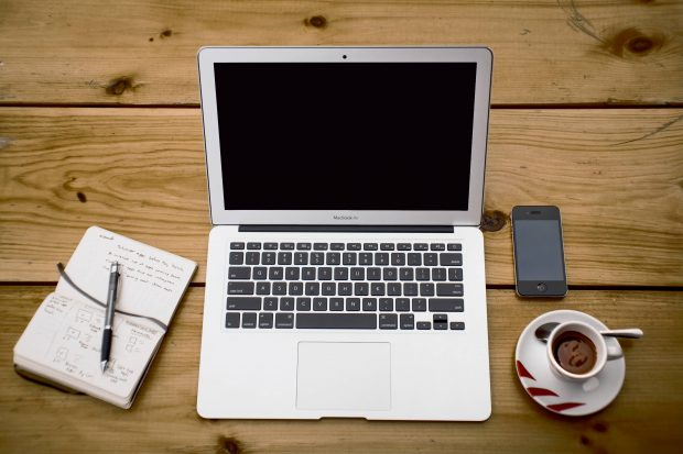 A desk with a laptop showing a blank screen, a notepad, a cup of coffee and a mobile phone