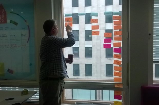 Mark Dalgarno (delivery manager at the Department for Education) looking at notes written on post-its