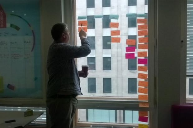 Mark Dalgarno (delivery manager at the Department for Education) looking at notes in a meeting