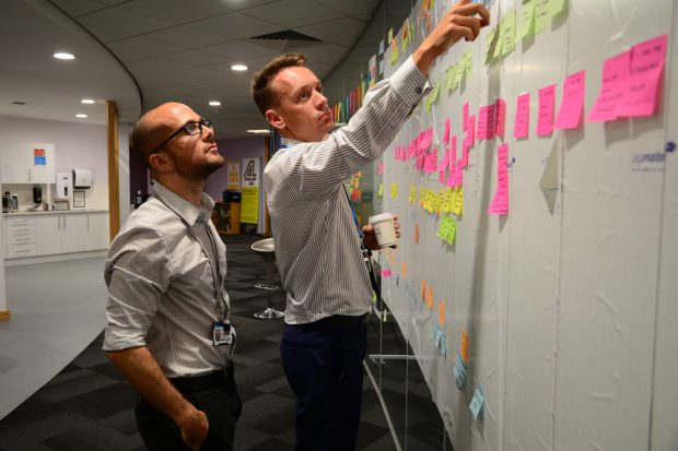 Product Manager, Andy, and another colleague having a meeting by the release wall