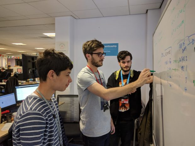 Arun, and two other apprenticeship service colleagues, standing next to a white board having a meeting
