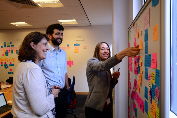 Three colleagues standing at a wall having a meeting, writing their ideas on post-it notes and sticking the notes to the wall.