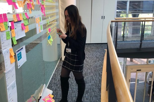 A typical day of a user researcher showing Lydia working on the User research wall in the office