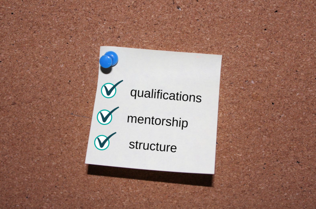 A note pinned to a noticeboard with the words qualifications, mentorship and structure written as a list