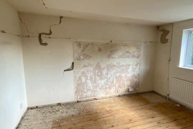 Interior house wall with cracked and damaged plaster board.